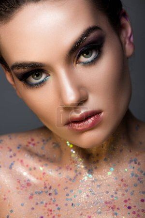 elegant glamorous girl posing with glitter on body, isolated on grey
