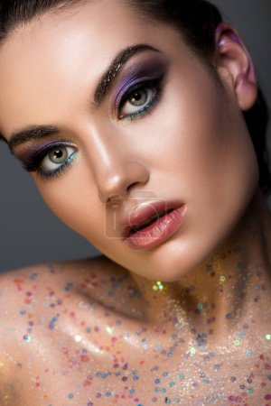 fashionable glamorous girl posing with glitter on body, isolated on grey
