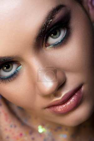 Close up of young woman with glitter makeup looking at camera