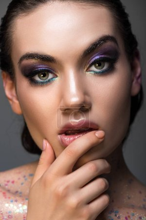 thoughtful girl posing with glamor makeup and glitter on body, isolated on grey