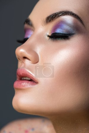 sensual young woman with closed eyes and glitter eyeshadows, isolated on grey