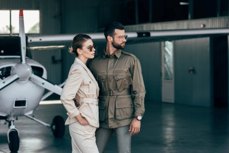 fashionable young couple in jackets looking away near airplane in hangar