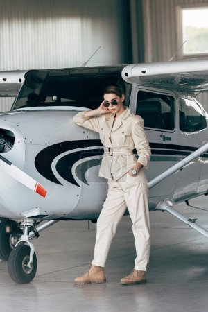 fashionable young woman in sunglasses and jacket posing near aircraft in hangar