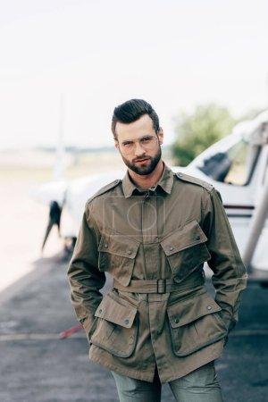 stylish man in green jacket and eyeglasses posing with hands in pockets near airplane