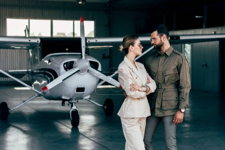 stylish young couple in jackets looking at each other near airplane in hangar