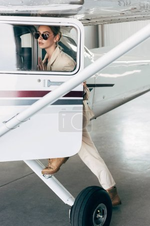 stylish young woman in sunglasses and jacket boarding in aircraft