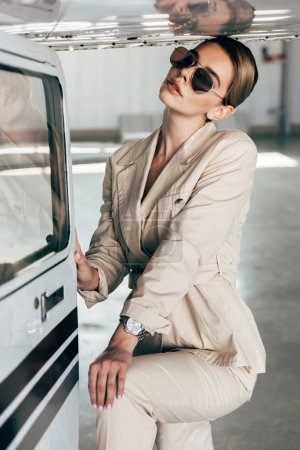 fashionable young woman in sunglasses and jacket posing near aircraft