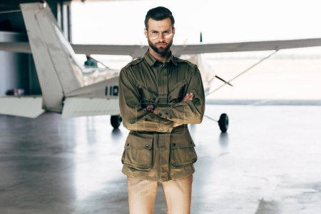 confident fashionable young man in green jacket and eyeglasses posing with crossed arms near airplane in hangar