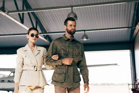low angle view of fashionable young couple in jackets walking near airplane in hangar