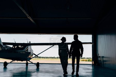 rear view of silhouettes of young couple walking near airplane in hangar