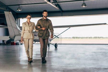 Foto de Seguro joven pareja moda en chaquetas de caminar cerca de avión en el hangar - Imagen libre de derechos