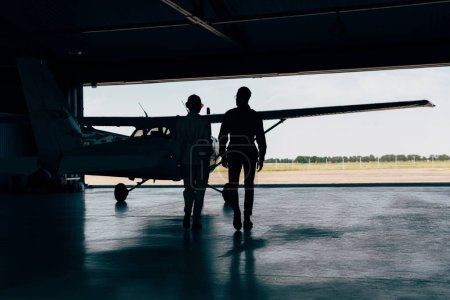 rear view of silhouettes of stylish couple walking near airplane in hangar