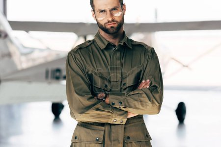 Photo for Handsome young man in green jacket and eyeglasses standing with crossed arms near airplane - Royalty Free Image