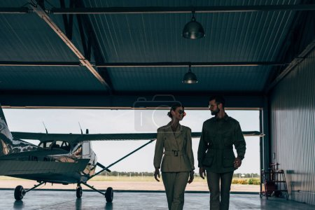 happy stylish young couple in jackets walking near airplane in hangar