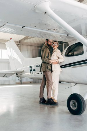 young fashionable couple in jacket embracing near plane in hangar