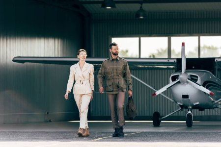 handsome man carrying bag and walking with stylish girlfriend near hangar with plane