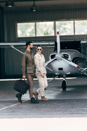 stylish man carrying bag and walking with girlfriend near hangar with plane