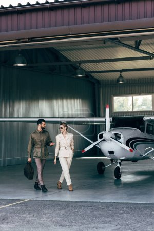 young man with bag gesturing by hand and talking to attractive girlfriend in hangar with plane