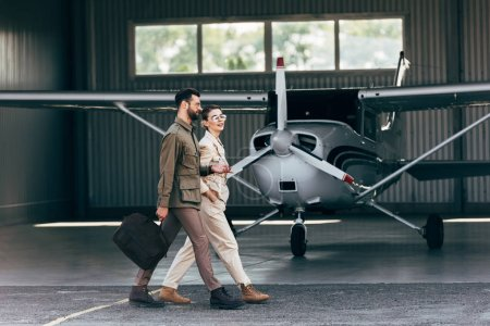 side view of man carrying bag and walking with stylish girlfriend near hangar with plane