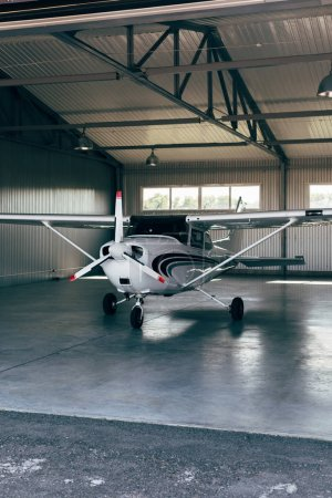 small modern white airplane standing in hangar