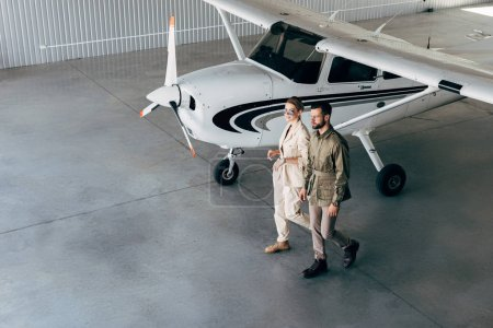 high angle view of fashionable young couple in stylish jackets walking in hangar with airplane