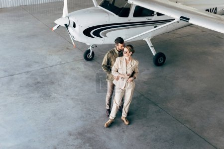 high angle view of young couple in stylish jackets embracing in hangar with airplane