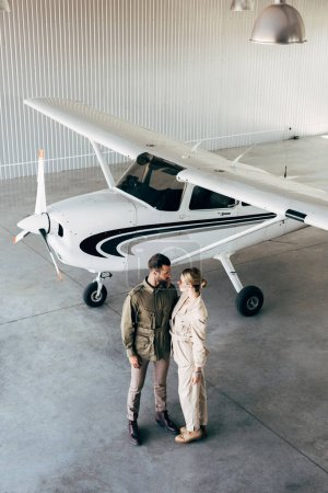 high angle view of couple in stylish jackets looking at each other in hangar with airplane