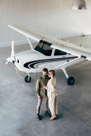 high angle view of fashionable young couple in stylish jackets embracing in hangar with airplane