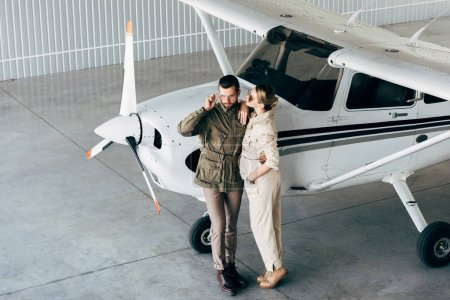 high angle view of fashionable young couple in stylish jackets standing near airplane in hangar