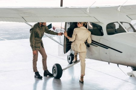 stylish young man opening door for girlfriend while she boarding in plane