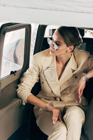 attractive young woman in sunglasses and jacket sitting in airplane