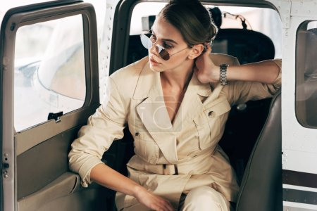 young stylish woman in sunglasses and jacket posing in airplane