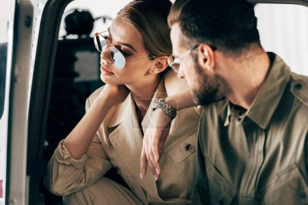 selective focus of attractive woman in sunglasses sitting in airplane while her boyfriend standing near plane