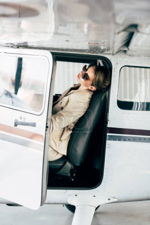 side view of stylish woman in sunglasses and jacket sitting in airplane