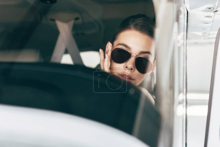portrait of beautiful young woman in sunglasses sitting in airplane