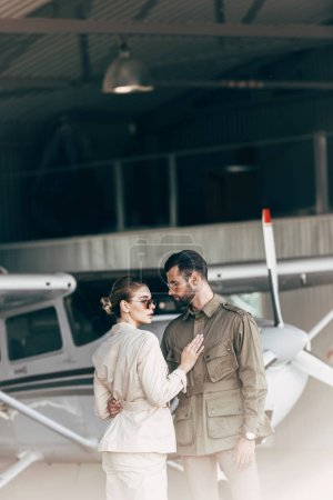 fashionable young couple in stylish jackets standing in hangar with airplane