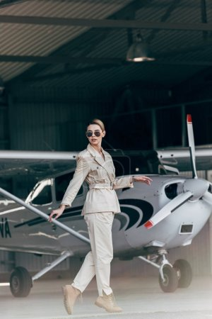 fashionable young woman in sunglasses and jacket posing near airplane