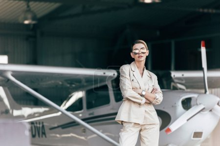 stylish young woman in sunglasses and jacket posing with crossed arms near aircraft