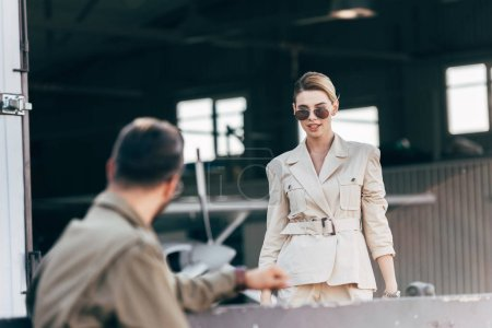 selective focus of beautiful young woman in sunglasses and jacket walking to boyfriend near hangar with plane