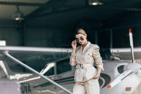 attractive young woman in sunglasses and jacket posing near aircraft