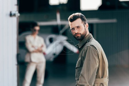 portrait of handsome man in eyeglasses and jacket looking at camera while his girlfriend standing in hangar with plane