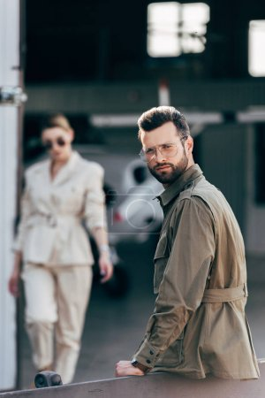 selective focus of stylish man in eyeglasses and jacket looking at camera while his girlfriend walking near hangar with plane