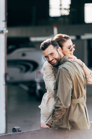 happy man in eyeglasses and jacket looking at camera while embracing girlfriend near hangar with airplane