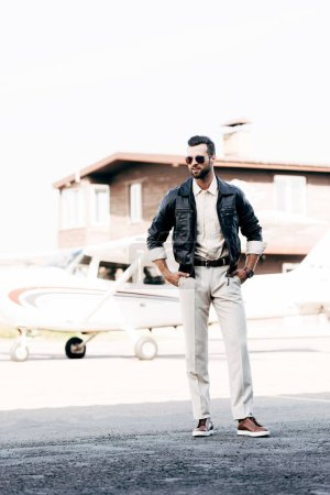 smiling fashionable male pilot in leather jacket and sunglasses standing with hands on waist near plane
