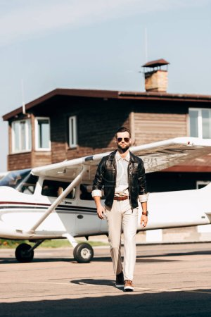 confident stylish male pilot in leather jacket and sunglasses walking near plane