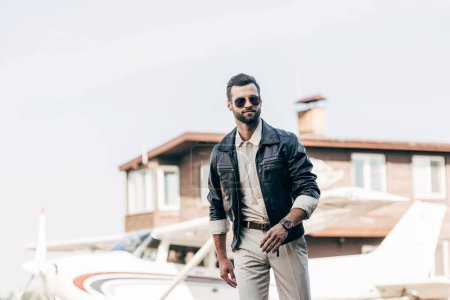 selective focus of fashionable male pilot in leather jacket and sunglasses walking near plane