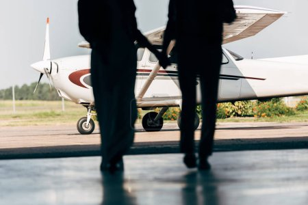 Photo for Cropped image of silhouettes of young couple holding hands and walking to airplane - Royalty Free Image