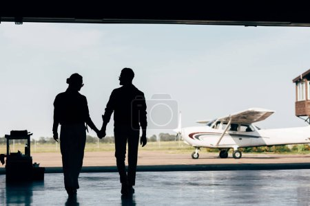 rear view of silhouettes of young couple holding hands and walking in hangar near airplane