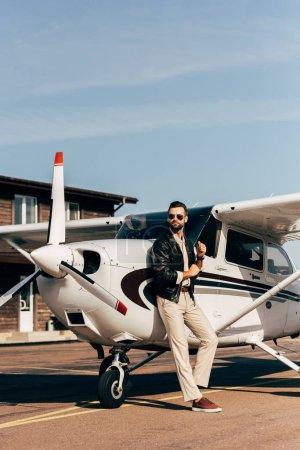 stylish man in leather jacket and sunglasses standing near airplane