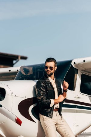 male pilot in leather jacket and sunglasses looking away near aircraft